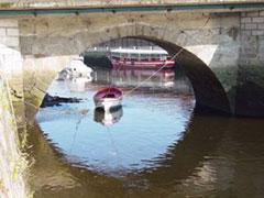 Uno de los arcos del Puente Viejo, con una barca de los Caneiros al fondo