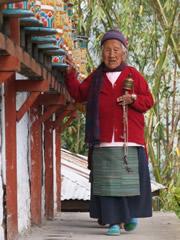 señora con molinillos de oración en Tashiding